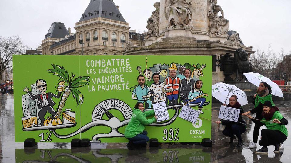 Oxfam-Aktivisten protestieren auf dem Platz der Republik in Paris