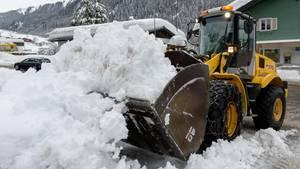 Ein Schaufellader räumt Schnee von einer Straße in Vorarlberg