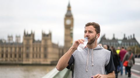Ein Jogger steht vor dem Big Ben und trinkt aus einer Plastikflasche