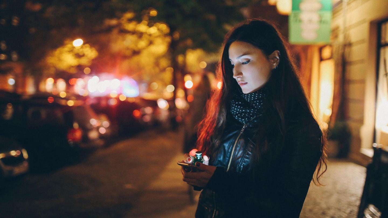 Heimwegtelefon: eine Frau steht nachts alleine auf der Straße