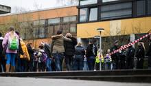Vor der Käthe-Kollwitz-Gesamtschule in Lünen stehen Polizisten, Schülerinnen und Schüler, einige halten sich gegenseitig im Arm