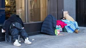 Obdachlose sitzen in vielen Schichten Kleidung auf dem Bürgersteig