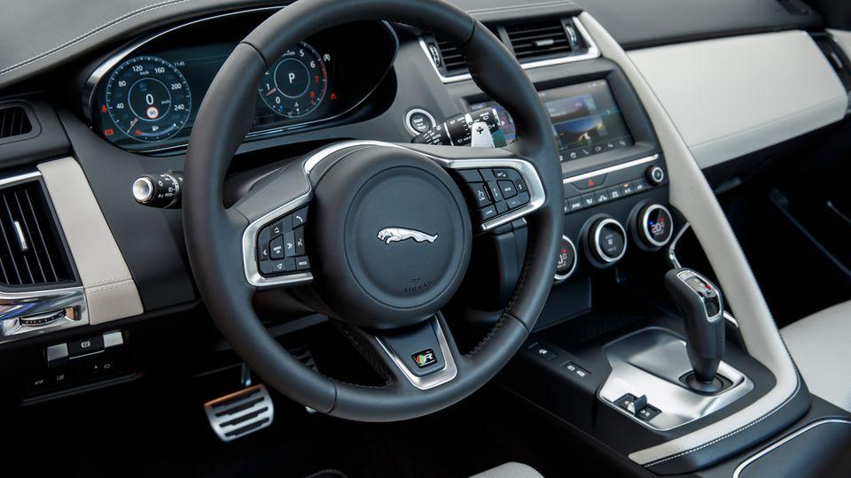 Das Cockpit des Jaguar E-Pace wirkt aufgeräumt und elegant. Der Haltegriff für den Frontpassagier ragt wie eine Bogenbrücke aus dem Armaturenträger und unterteilt Fahrer- und Beifahrerplatz.