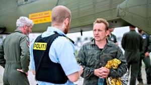 In Tarnfleck und mit einer Rettungsfolie im Arm steht Peter Madsen vor einem Flugzeug und spricht mit einem Polizisten