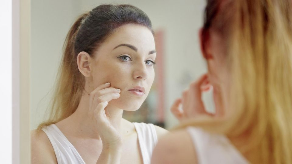 Eine junge Frau mit Akne betrachtet sich im Spiegel