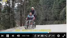 Großmutter schiebt im Rollstuhl sitzenden Enkelsohn zur Schule