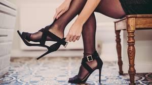 Eine Frau im schwarzen Minikleid sitzt und zieht sich mit übereinander geschlagenen Beinen einen High Heel an den rechten Fuß