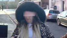In einer Jacke mit Tierprint wird die Frau zum Gericht geführt