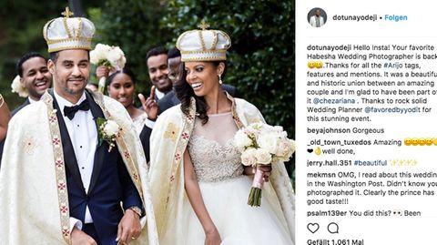 Fröhlich lachend schreitet das Brautpaar vor seinen Gästen durch einen Park
