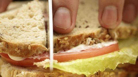 Auf einem Holzbrett liegt ein Sandwich. Vier Finger halten das Sandwich, während eine Messerklinge es durchschneidet.