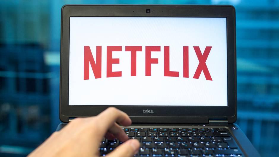 """Ein Laptop-Bildschirm zeigt auf weißem Grund den roten """"Netflix""""-Schriftzug. Eine linke Hand liegt auf der Tastatur"""