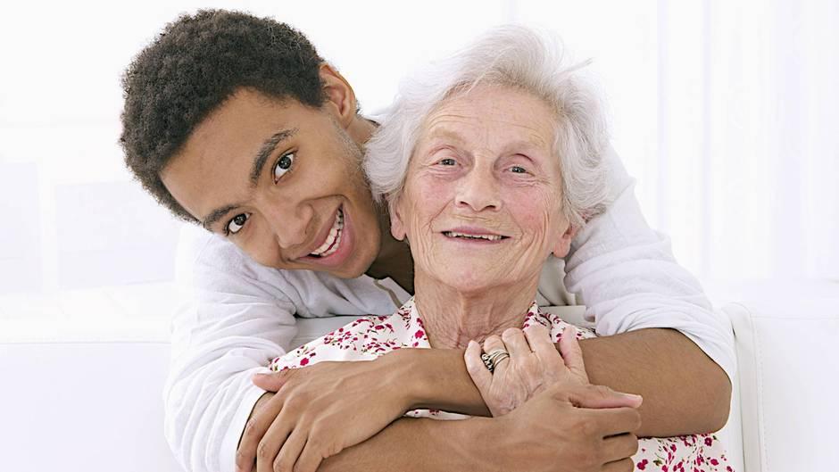 Eine Oma wird von ihrem Enkel liebevoll umarmt