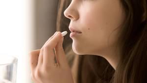 Eine Frau nimmt eine Tablette ein.
