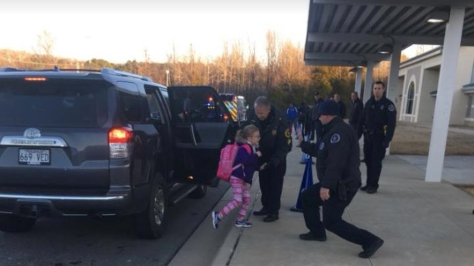Polizisten tanzen, um Schulkinder zu begrüßen
