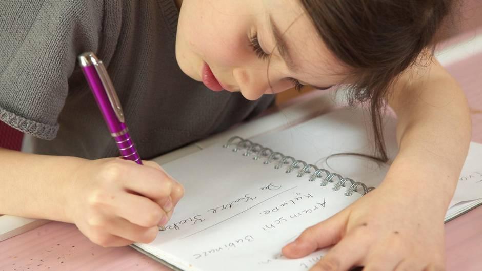 Eine Grundschülerin beugt sich über einen Block und schreibt mit einem Kugelschreiber einen Satz.