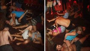 Ein dutzend jüngere Erwachsene tanzen auf dem Boden liegend miteinander auf einer Party in Kambodscha.