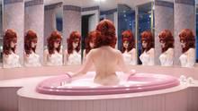 Eine nackte Frau sitzt in einer herzförmigen Badewanne in einer Honeymoon Suite