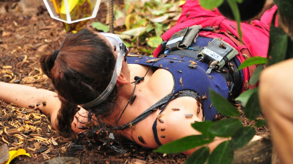 Kattia Vides zappelt und versucht so die Kakerlaken von ihren Beinen zu bekommen