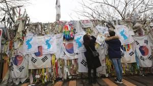 Besucher fordern mit Flaggen an einem Grenzzaun die Wiedervereinigung von Süd- und Nordkorea