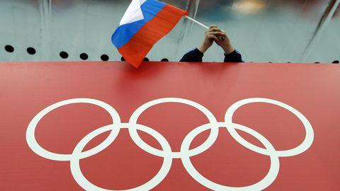 Fan schwenkt Russland-Flagge, darunter olympische Ringe. CAS hebt Sperren für Olympia für russische Sportler auf