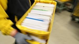 Ein Postbeamter trägt eine Kiste voller Briefe