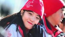 Freiwillige Helferin grüßt in die Kamera - Olympia-Dorf in Pyeongchang ist eröffnet