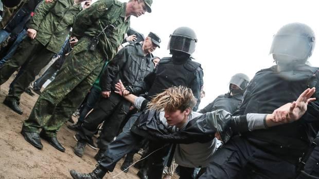Ein Jugendlicher wird während der Proteste vom vergangenen Juni von Polizisten abtransportiert