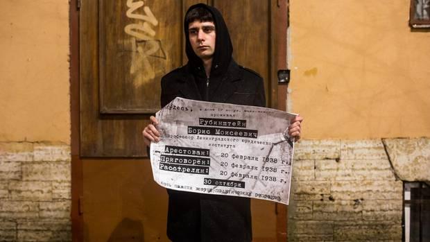 Mit einem Plakat erinnert ein junger Mann von Wesna an die Opfer der Stalin-Zeit