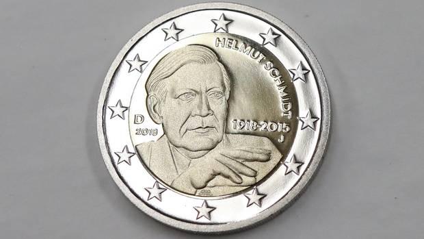 Auf einer Zwei-Euro-Münze liegt auf grauem Untergrund. Auf der Münze ist Altkanzler Helmut Schmidt zu sehen - ohne Zigarette