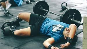 Ein Mann liegt im Fitnessstudio am Boden