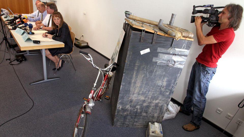 Ein Nachbau der Kiste und das rote Fahrrad von Ursula Herrmann bei einer Pressekonferenz 2008