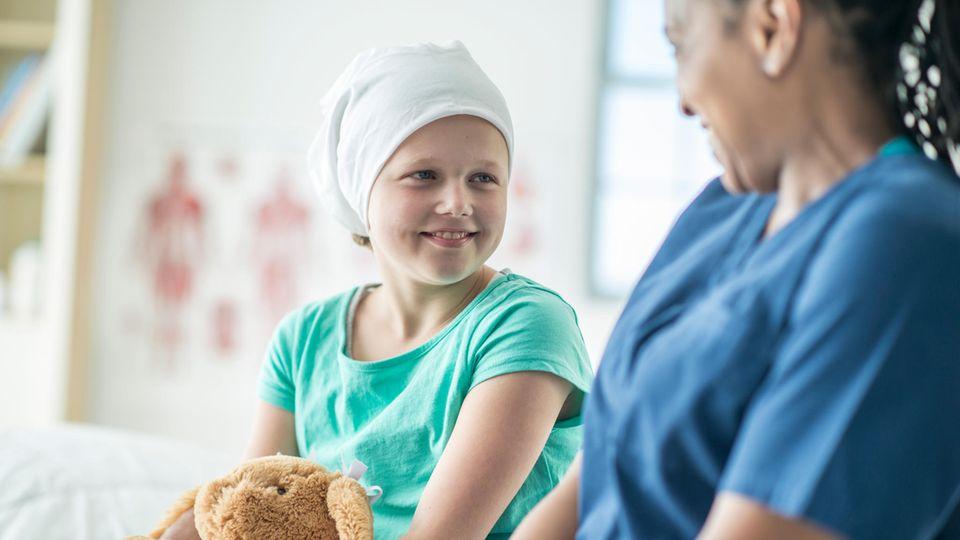 Schwerkrankes Kind mit Kuscheltier und Krankenschwester