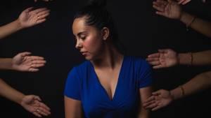 Frau alleine, nach der viele Hände greifen