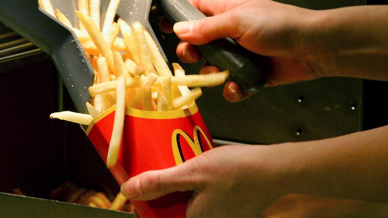 Ein McDonald's-Mitarbeiter füllt Pommes ein