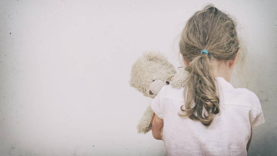 Rücken eines Mädchen mit Teddybär im Arm