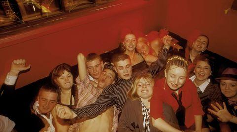 Eine Gruppe Jugendlicher feiert in einer Kneipe