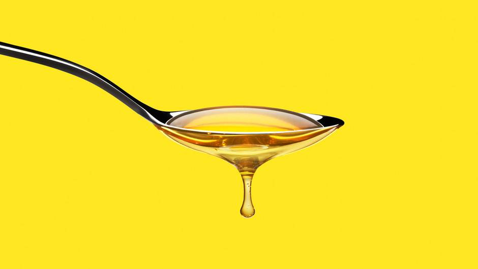 Ein Löffel, von dem Honig tropft