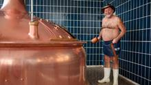 Bierbrauer Jürgen Hopf aus Oberfranken steht nur emit Schürze, Hut und Gummistiefel bekleidet in der Lang-Bräu-Brauerei.