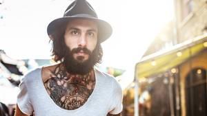 T-Shirt: Tätowierter junger Mann in weißem T-Shirt mit Hut