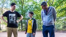 Michel Abdollahi steht mit zwei Jugendlichen auf einem Bolzplatz