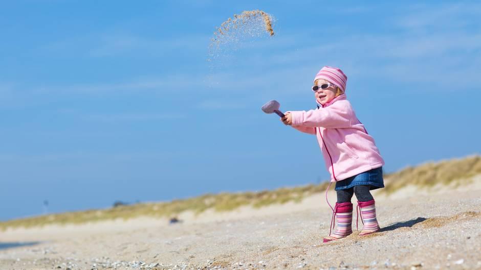 Ein Mädchen in wetterfester Kleidung wirft eine Schaufel voll Sand in die Luft