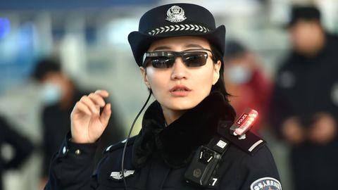Eine Polizistin an einem Bahnhof in China mit den neuen Sonnenbrillen mit integrierter Software für Gesichtserkennung