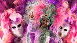 Diese Tänzerinnen der Sambaschule Mangueiraschmücken sichmit Federn, Flügeln und Masken.