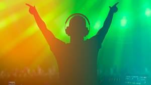 Ein DJ steht im Gegenlicht in einer Disco und reckt die Arme nach oben