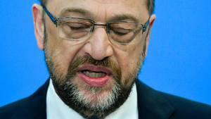 Der bisherige SPD-Vorsitzende Martin Schulz steht im Anzug vor einer blauen Wand und sieht enttäuscht aus