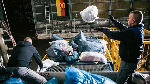 In dreißig Minuten schaffen die beiden Männer zwölf Tonnen mit Textilien, Schuhen oder Bettdecken weg