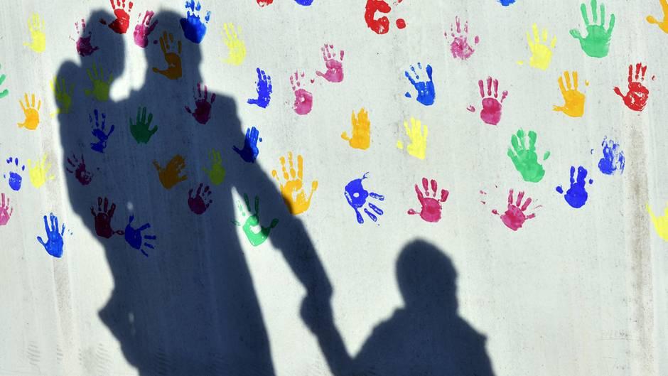 Der Schatten eines Mannes mit zwei Kindern an der Wand einer Kindertagesstätte