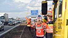 """Rettungskräfte sichern eine Unfallstelle auf der Autobahn A5, ein Feuerwehrmann winkt in Richtung Gegenfahrbahn, wo zahlreiche """"Gaffer"""" den Verkehr behindern."""