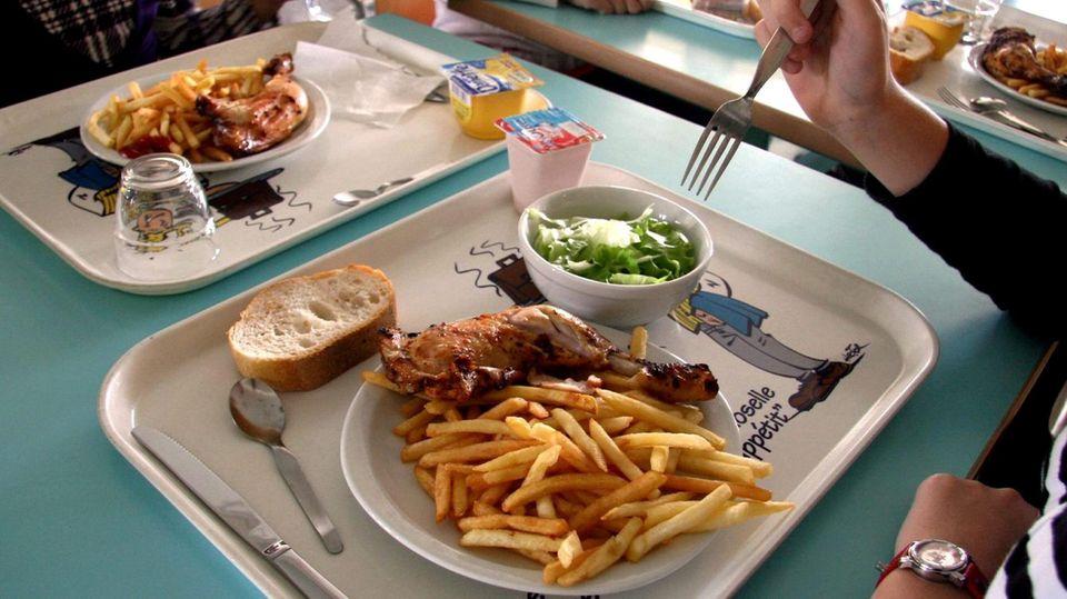 Auf einem Tablett ist ein Teller mit Pommes und einer Hähnchenkeule, eine Schale Salat und ein Stück Brot.