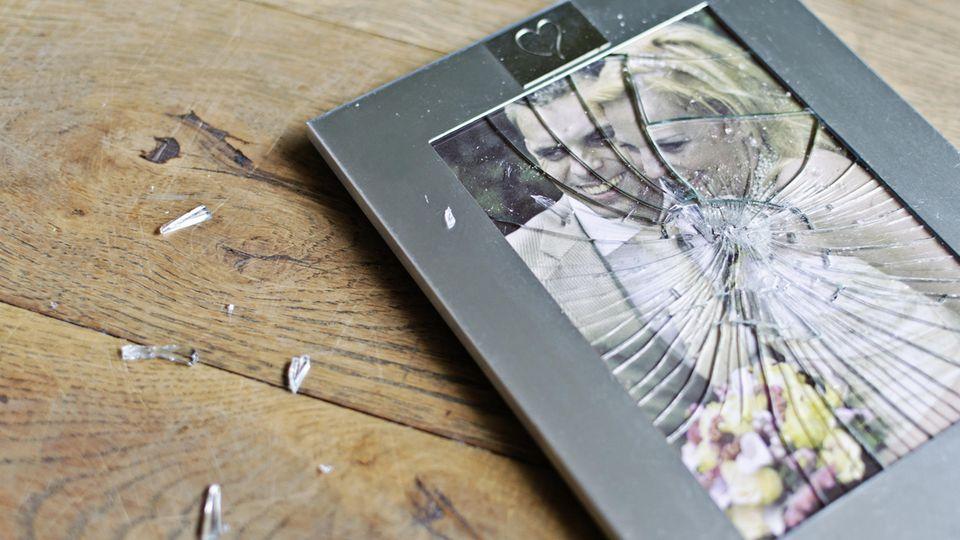 Ein Pärchen-Foto in einem zersprungenen Bilderrahmen